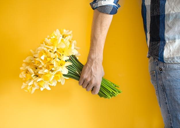 ジーンズと水仙の大きな花束を持っているシャツの男性。女性の日のコンセプトとおめでとうございます。 Premium写真