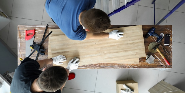 男性のジョイナーは、テーブルの上の木製の表面のキャンバスを磨きます。ワークピースを処理するためのさまざまなツールを表面の作業台に設置します。特別な大工道具と適切に設備された職場 Premium写真