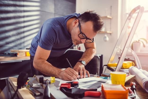 Men looking at blueprints during kitchen renovation Premium Photo