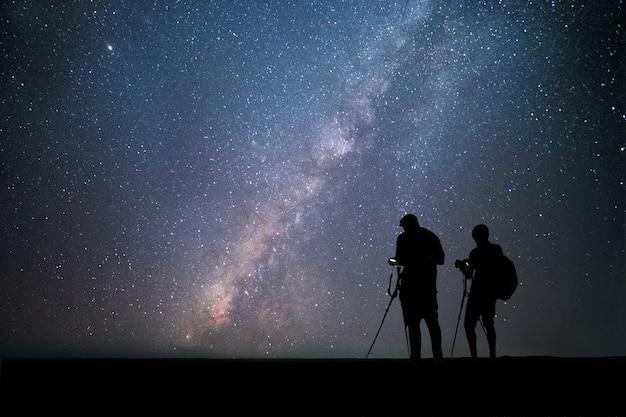 Men photographer standing near the camera and taking photo milky way and stars Premium Photo