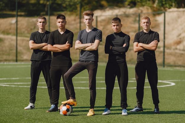 남자들은 공원에서 주술을한다. 미니 축구 토너먼트. 검은 Sportsuits에있는 남자. 무료 사진