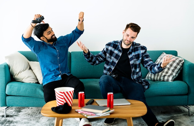 Men playing video game on sofa Premium Photo