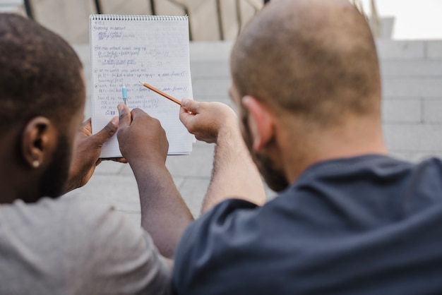 Men pointing at notebook outside Free Photo