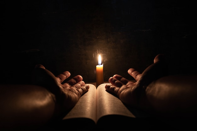 Люди молятся на библии в свете свечи селективного внимания. Бесплатные Фотографии