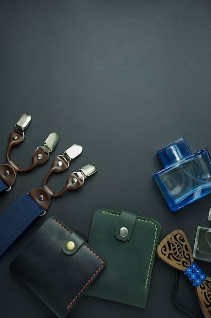 Men's accessories. men's wallet, men's butterfly, suspenders and perfume on a dark background. Premium Photo