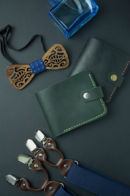 Men's accessories. men's wallet, men's butterfly, suspenders and perfume on a dark background. Premium Photo