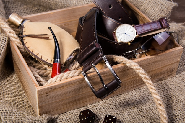 Men's accessories with brown leather belt, sunglasses, watch, smoking pipe and bottle with perfume Premium Photo