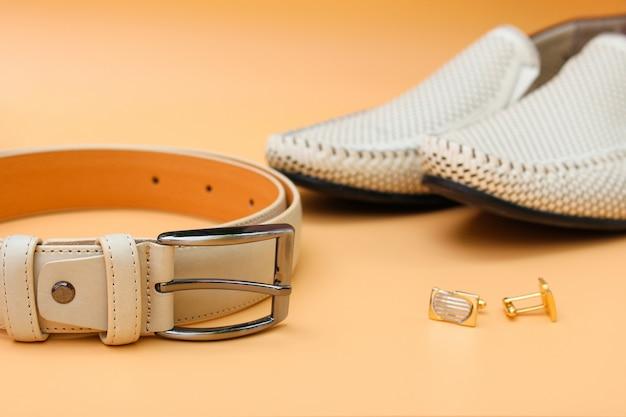 Men's belt, shoes, cufflinks on beige background. Premium Photo