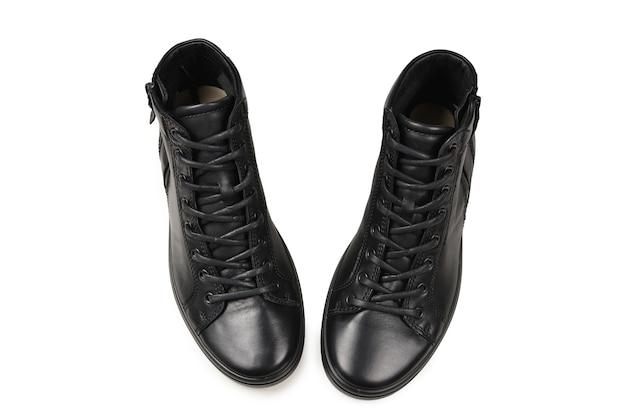 男性の黒い革の靴と白い背景で隔離の黒いカメラ。スペースをコピーします。 Premium写真