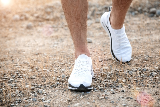 Men's feet in white sneakers running over rough terrain. cross country running with focus on runner's legs. Premium Photo