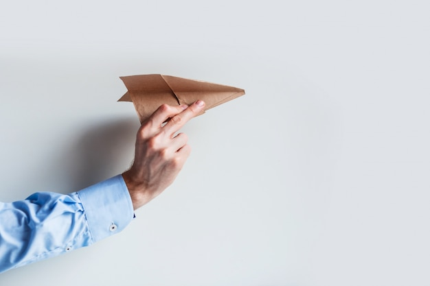 Men's hand in a blue shirt uniform launches a paper airplane. Premium Photo