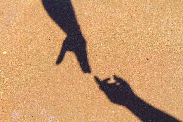 Men's hand reaches for women's hand shadow on sand background Premium Photo