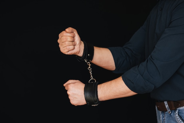 Men's hands chained in leather handcuffs on black Premium Photo