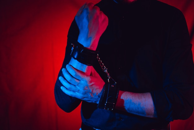 Men's hands chained in leather handcuffs Premium Photo