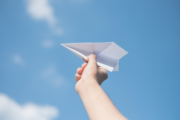 Men's hands holding a white paper rocket with a bright blue background. Premium Photo