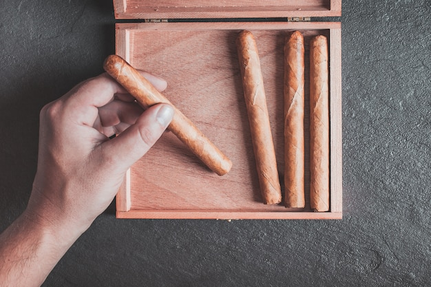 Men's hands take a cigar out of the box on a dark table Premium Photo