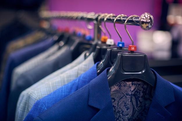 Men's jackets on hangers in the men's store Premium Photo