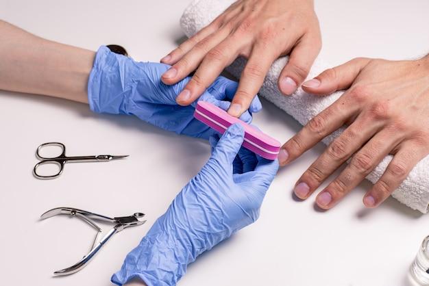 男性用マニキュア。ゴム手袋の美容師は、男性の手に爪を打ちます。 Premium写真