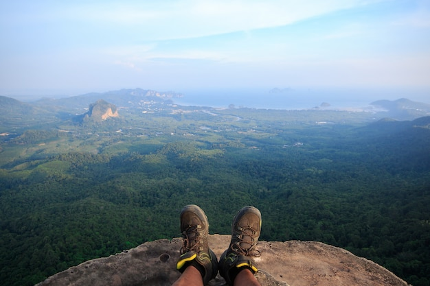 Men's shoes on the cliff there is a view below the forest. Premium Photo