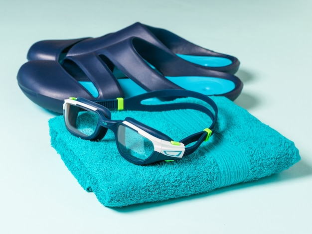 Premium Photo | Men's swimming goggles on a towel and blue slates.  accessories for swimming in the pool.