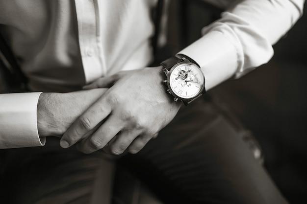 Мужские наручные часы, мужчина смотрит время. часы бизнесмена, бизнесмен проверки времени на его наручных часах. руки жениха в костюме, регулирующие наручные часы, аксессуары жениха. Premium Фотографии