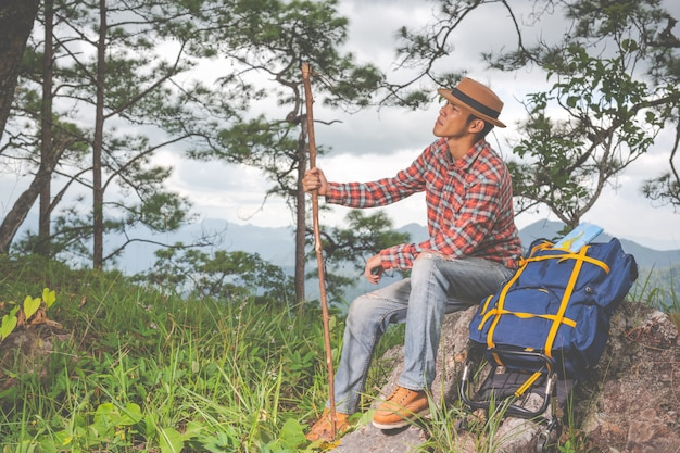 Men sit and watch mountains in tropical forests with backpacks in the forest. adventure, traveling, climbing. Free Photo