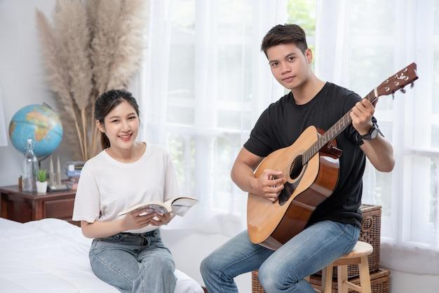 Мужчины сидят на гитаре и женщины держат книги и поют. Бесплатные Фотографии