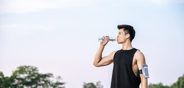 男性は運動後に水を飲むために立ちます 無料写真