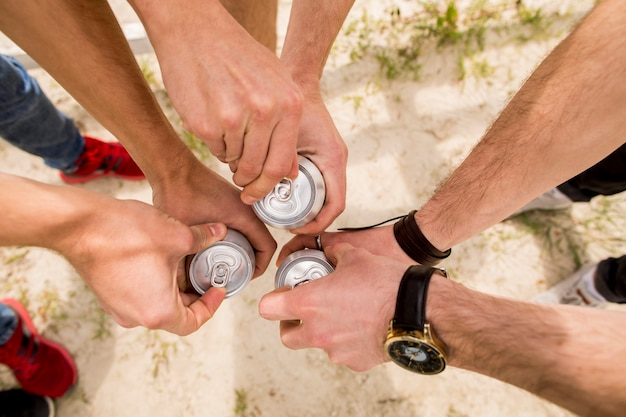 Men standing close together and opening beer Free Photo