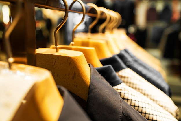 Men suits hanging in a clothing store. Premium Photo