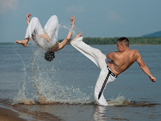 Men train capoeira on the beach - concept about people, lifestyle and sport. Premium Photo