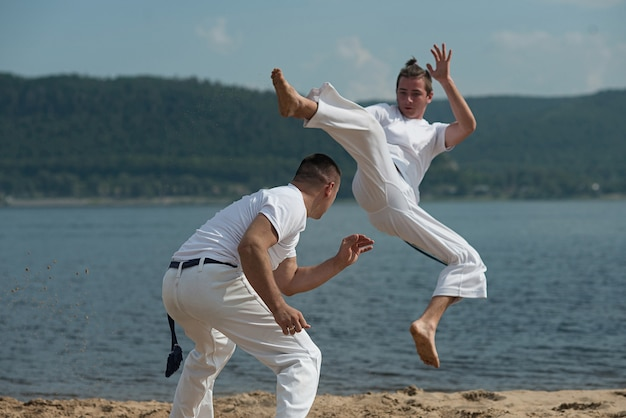 Men train capoeira on the beach Premium Photo