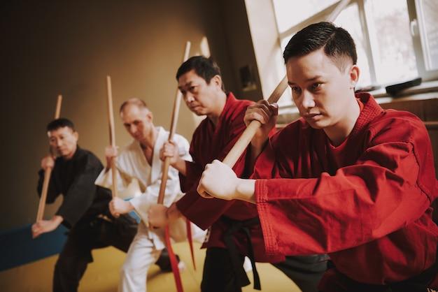 Men in training practice methods with sticks. Premium Photo
