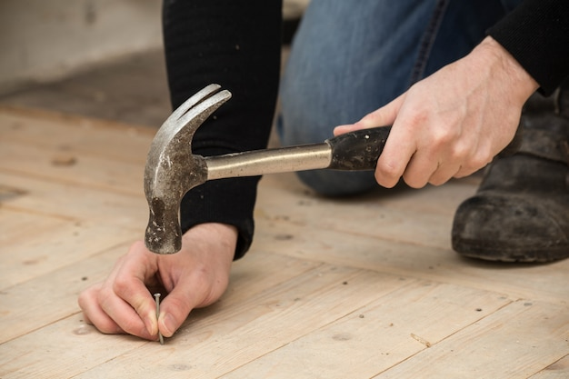 Men using a hammer and nail on wood , renovation concept Premium Photo