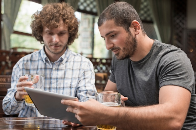 Men using tablet in pub Free Photo