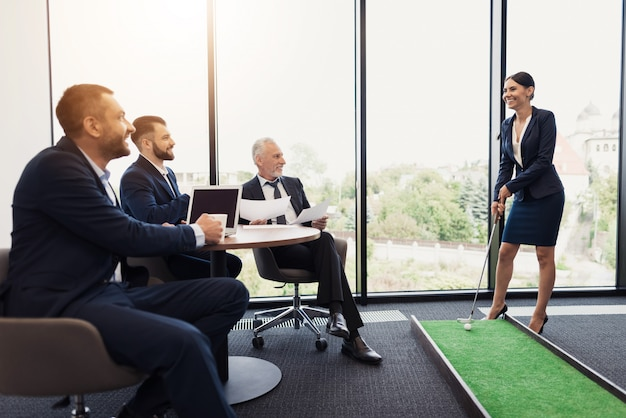 Men watch haw woman in a business suit playing mini golf Premium Photo