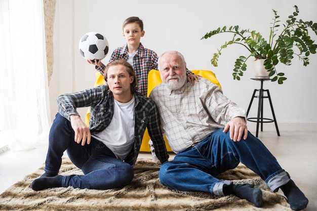 Men watching football sitting on carpet at home Free Photo