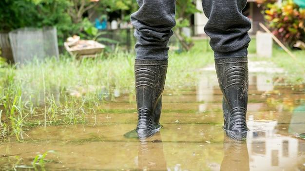 Men wear black boots for a flood. Premium Photo