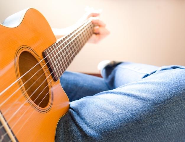 Мужчины носят джинсы и сидят на акустической гитаре. Premium Фотографии