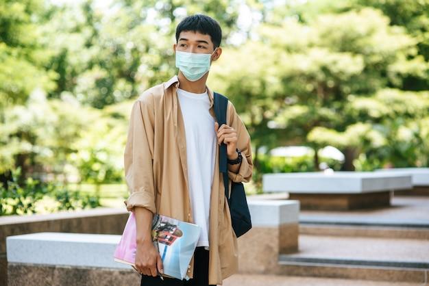 Gli uomini indossano maschere, portano libri e portano uno zaino sulle scale. Foto Gratuite