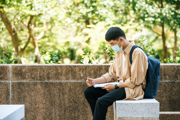 マスクをかぶった男性が階段で本を読んで座っています。 無料写真