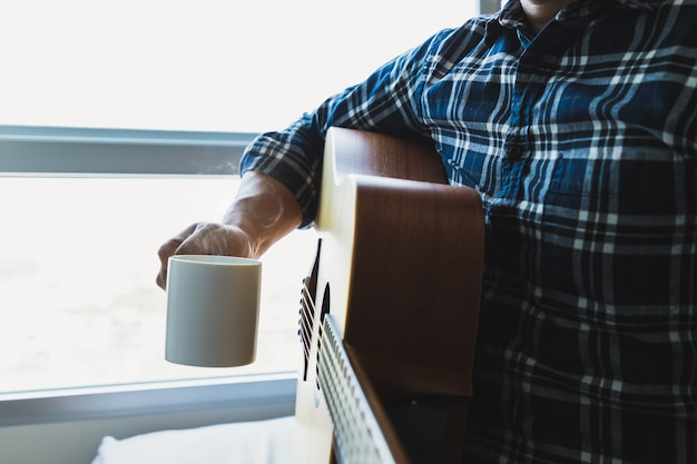 Men wearing a plaid shirt holding a coffee mug after playing the guitar Premium Photo