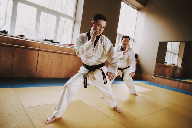 Men in white clothes and black belts train in the gym. Premium Photo