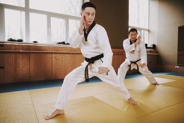 Men in white clothes and black belts train Premium Photo