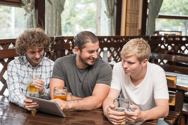 Men with beer using tablet and chatting in bar Free Photo