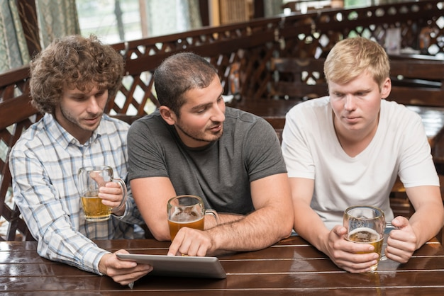 Men with tablet and beer talking in pub Free Photo