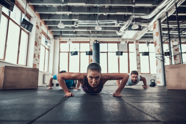 Men and woman doing push ups in the bright gym. Premium Photo