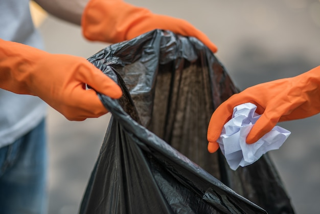 Men and women help each other to collect garbage. Free Photo