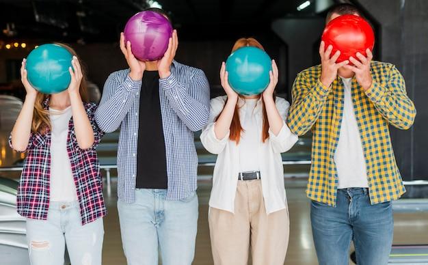 Uomini e donne in possesso di una palla da bowling in testa Foto Gratuite