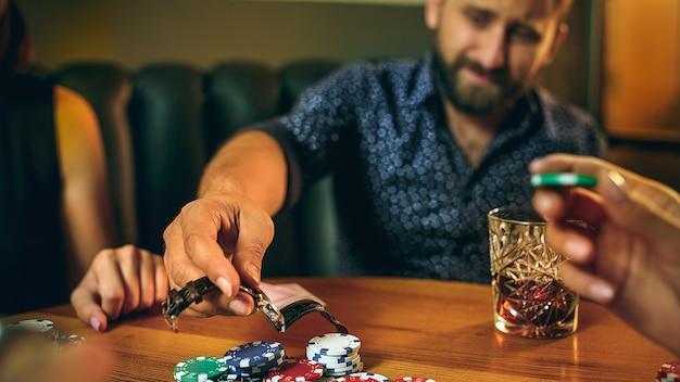Uomini e donne che giocano a carte. poker, intrattenimento serale e concetto di eccitazione Foto Gratuite
